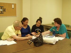 RSVP volunteer Jeff Knezel tutors Leticia Leon and Maria Leon, along with volunteer tutor Linda Kilas (right), during a financial literacy class held at First United Methodist Church in Appleton. Kilas is president of the board of Literacy Education Services, Inc., which provides classes to adults so they can achieve their maximum potential.