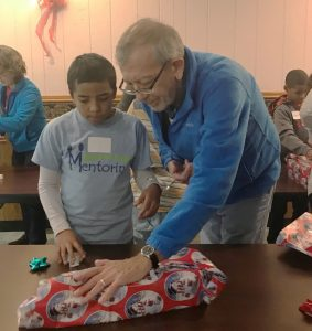 RSVP volunteer mentor, David Hinds, and his mentee, CJ, try to wrap a gift box with only one hand each during game time at a holiday party held in December for the Outagamie County Mentoring Program.