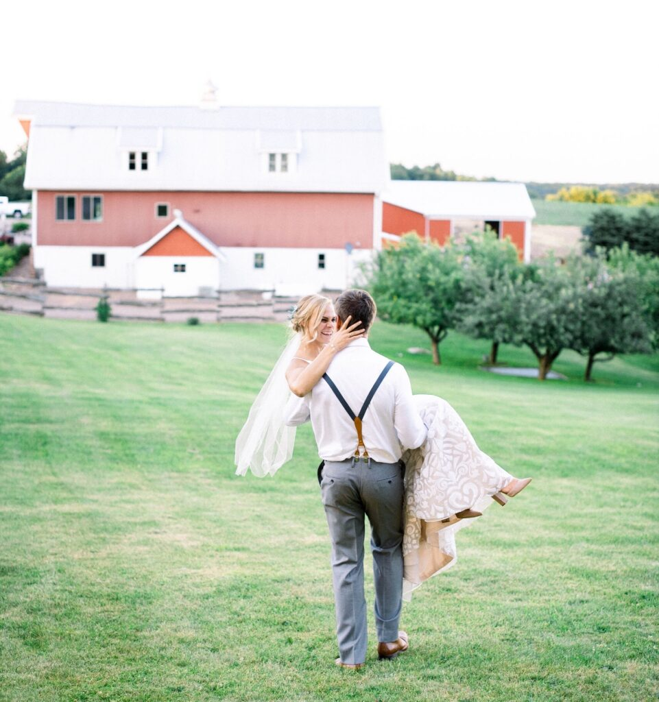 Groom carrying bride with barn in background
