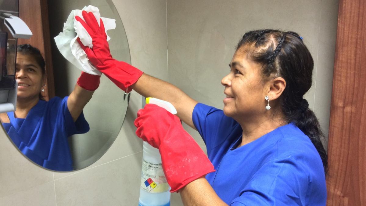 señora limpiando espejo