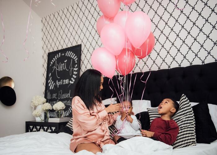 niños y mamá en la cama felices con unos globos