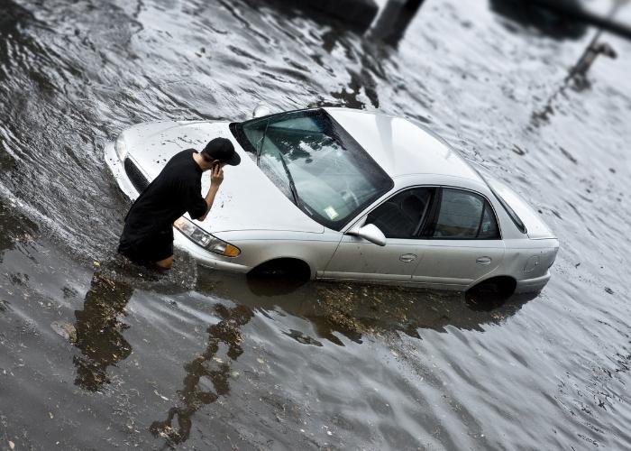 joven afuera de su auto inundado por las lluvias