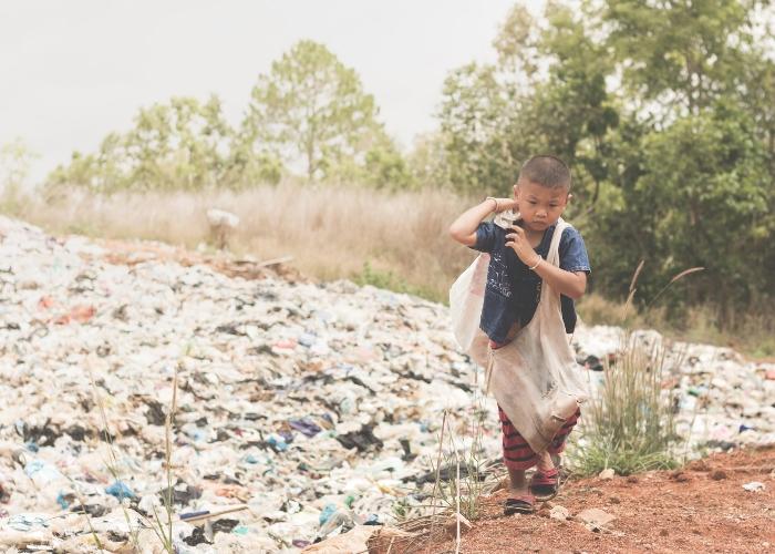 niño caminando entre basura