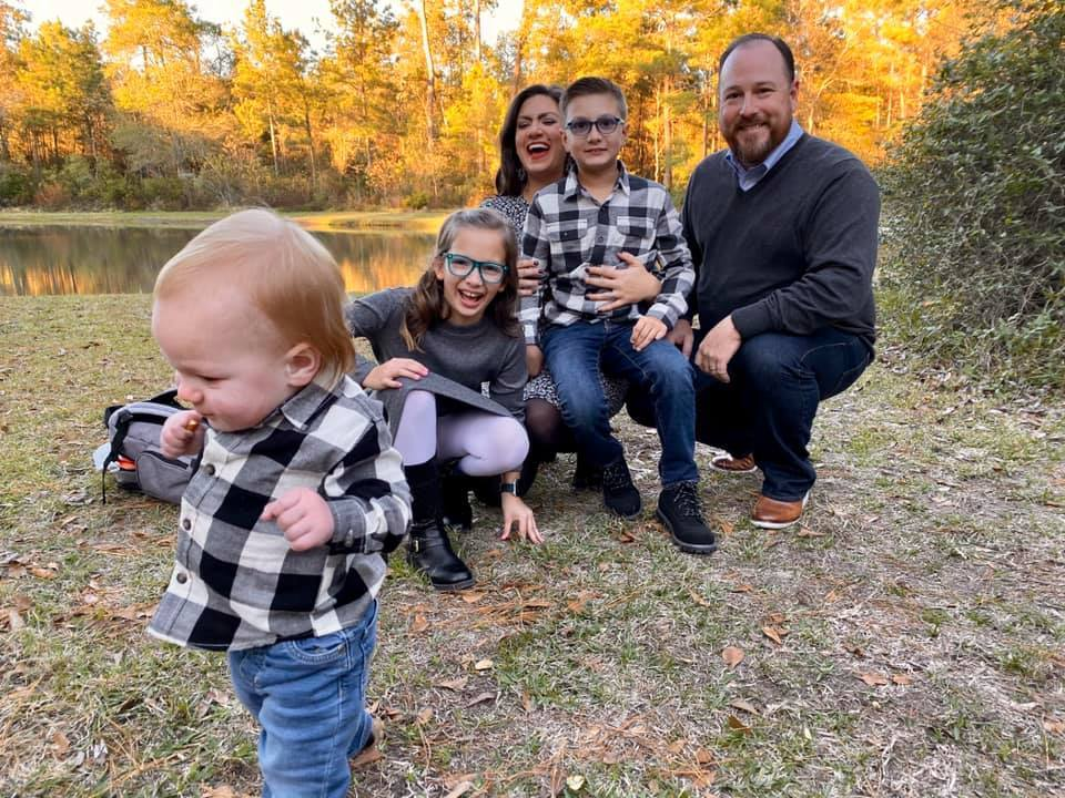 Jessica and her husband and children outdoors at sunset, laughing while the baby is running away from the picture