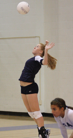 Senior Alyssa Micheletti serves in a volleyball match.