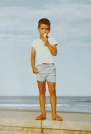 Who is this boy standing on a beach?