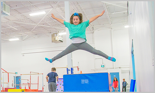 A smiling student jumps off the vault during a birthday party at AIM Gymnastics' Ajax location.