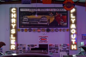 LIghted Chrysler Plymouth large vertical neon signs.