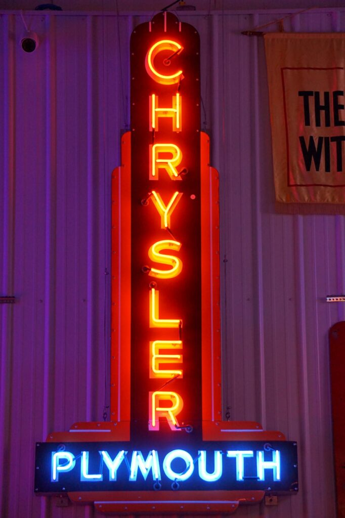 Lighted Chrysler Plymouth red and blue dealership neon sign.