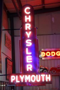Lighted Chrysler Plymouth red and white verticle dealership neon sign.