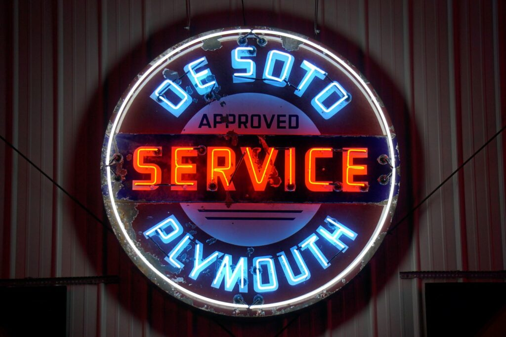 Lighted DeSoto Plymouth Approved Service round red and blue neon sign.