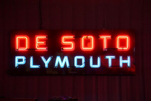 Lighted DeSoto Plymouth horizontal red and blue neon sign.
