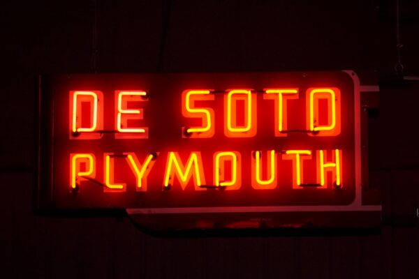 Lighted DeSoto Plymouth red horizontal neon sign.
