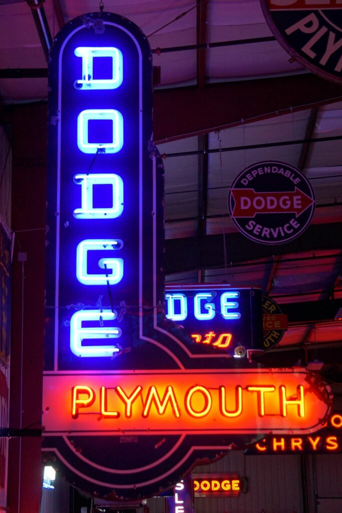 Lighted Dodge Plymouth vertical blue and red neon sign.