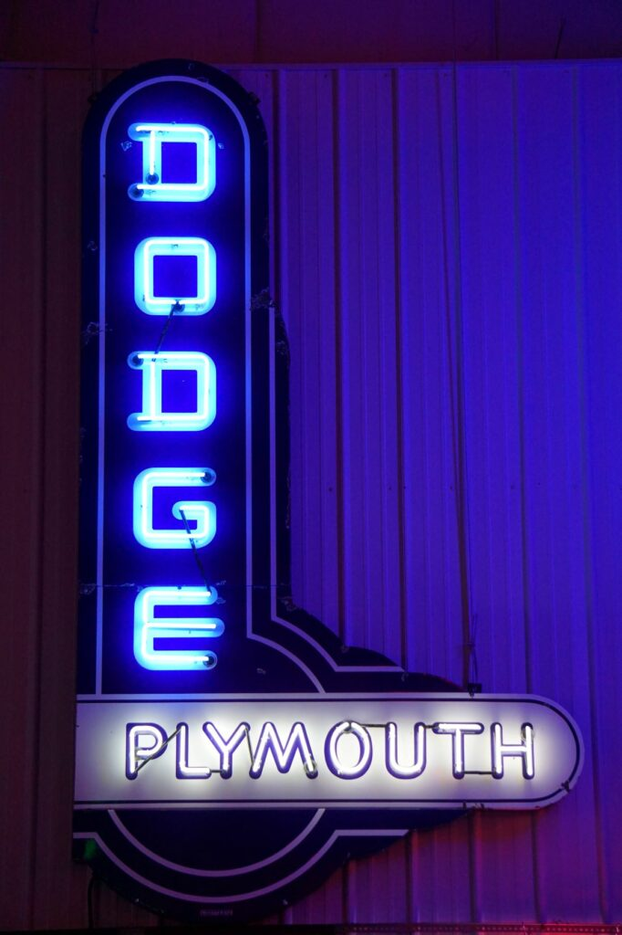 Lighted Dodge Plymouth vertical blue and white neon sign.