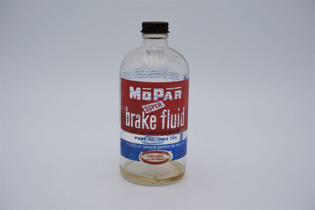 Antique Mopar Super Brake Fluid, 16 oz clear glass bottle.