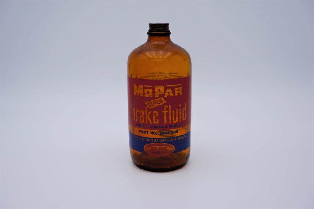 Antique Mopar Super Brake Fluid, 32 oz brown glass bottle.