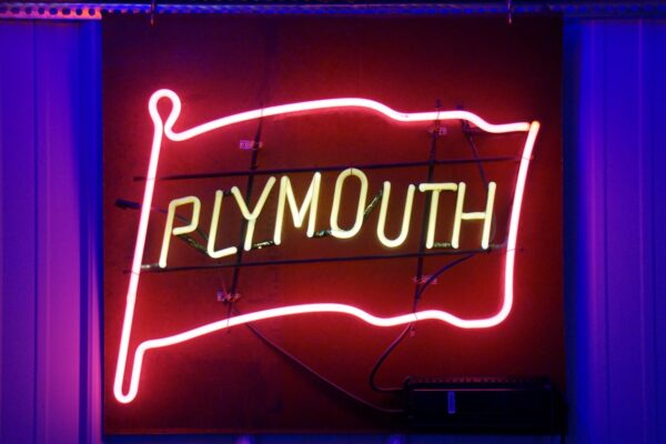 Lighted Plymouth red and yellow flag neon sign.
