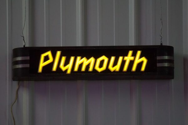 Lighted Plymouth yellow and black horizontal sign.