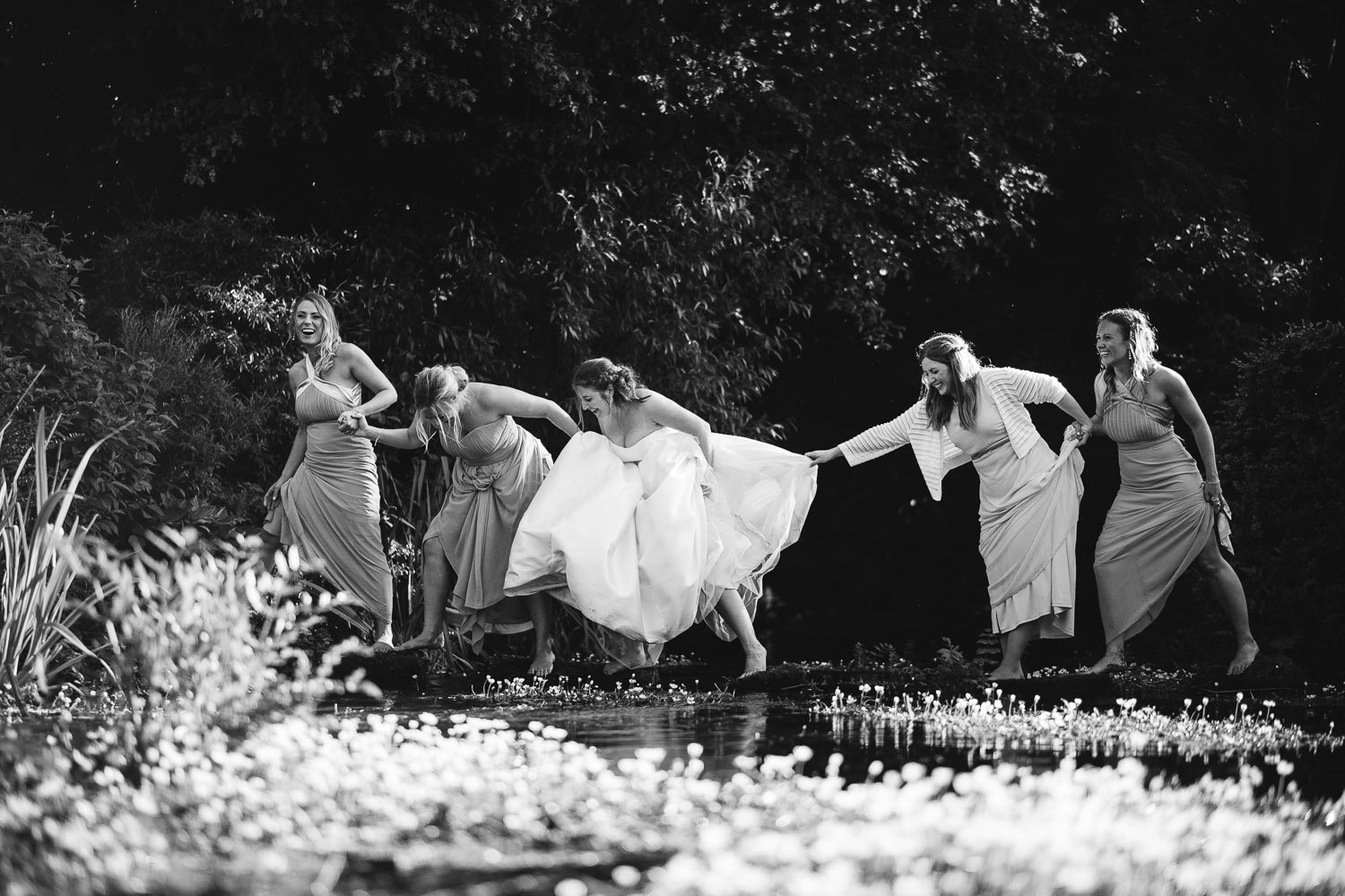 Bridesmaids cross a river