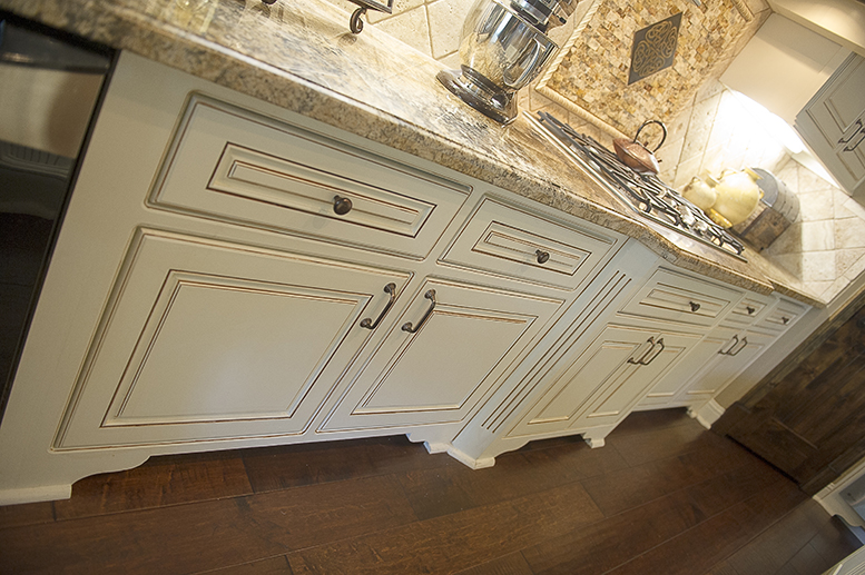 Check out the gorgeous flooring and the woodwork around the base of these custom cabinets.