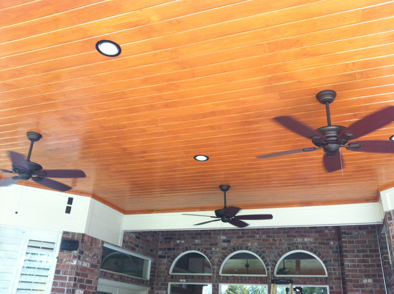 A natural wood ceiling is installed with inset lighting and ceiling fans - a must have in Texas!