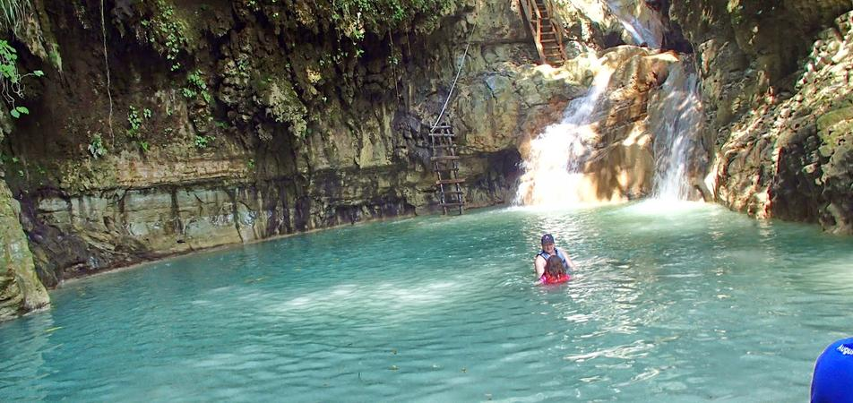Sliding through the waters between 2 cascades of Damajagua Falls