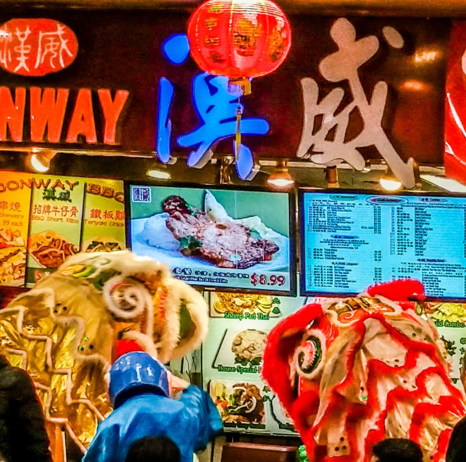 Lion dancers performing at one of the food joints in the Food Court at New World Mall, Chinatown, Flushing, NYC