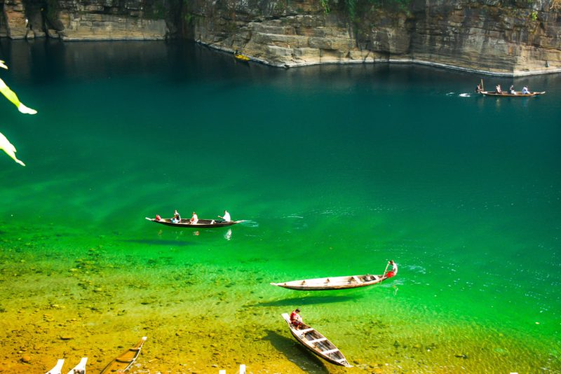 Levitating boats at crystal clear Umngot river on a sunny day. It is near the border of India/Bangladesh.