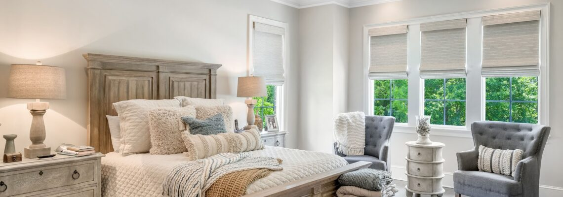 master bedroom with large wooden bed and three windows with neutral roman shades