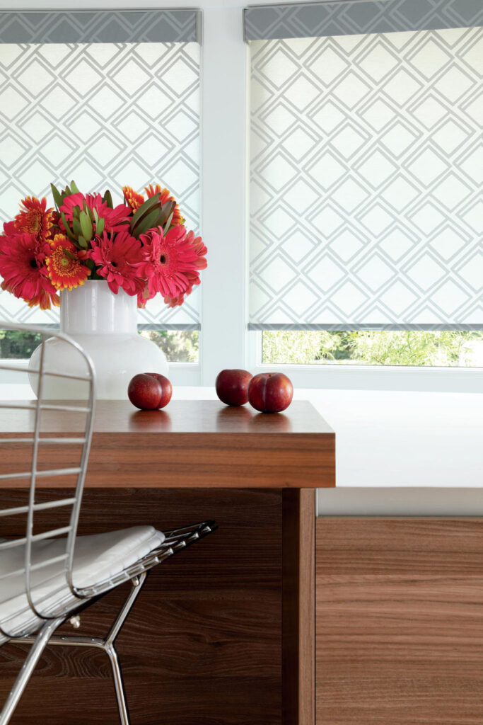 Roller shades in a kitchen with red daises in a vase on the counter