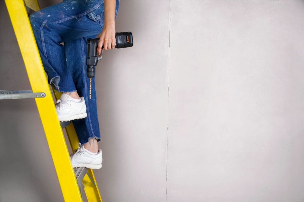 woman climbing ladder with power tool