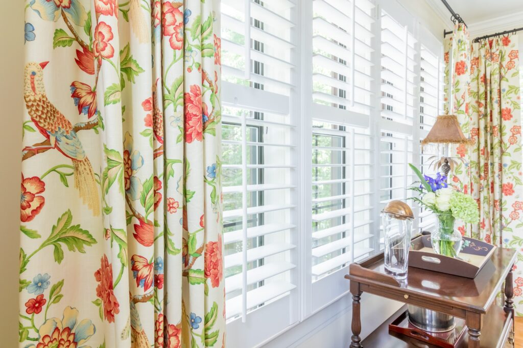 Draperies layered with plantation shutters