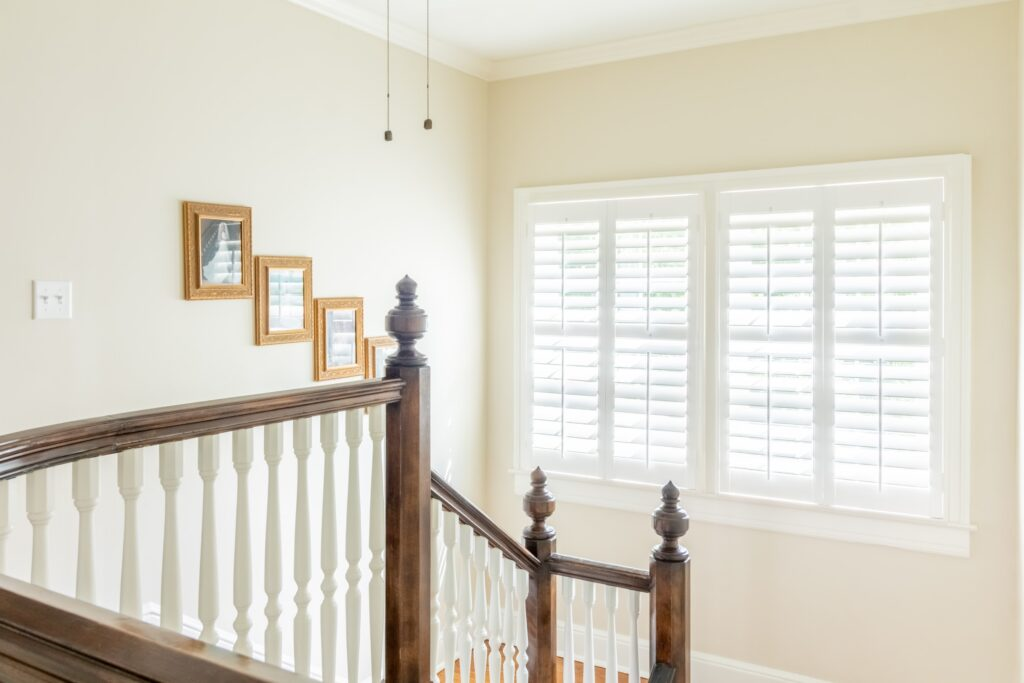 Stairwell in front of window with plantation shutters