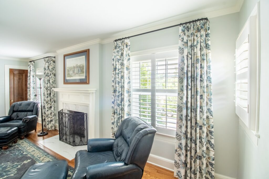 Blue and white drapery layered with plantation shutters between a fireplace.