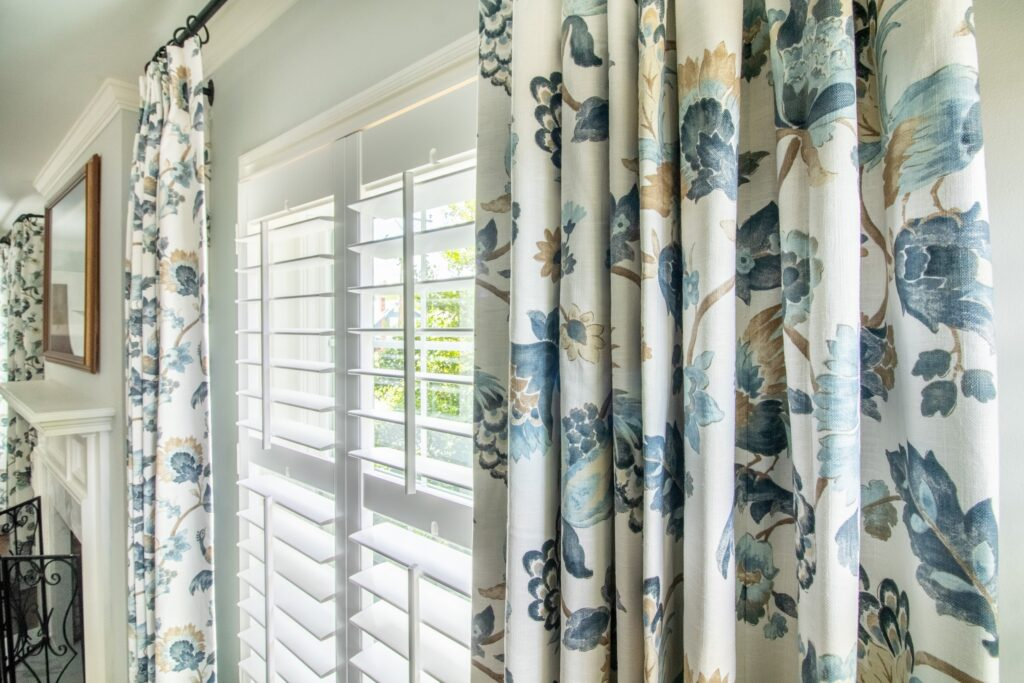Blue and white floral drapery layered with plantation shutters