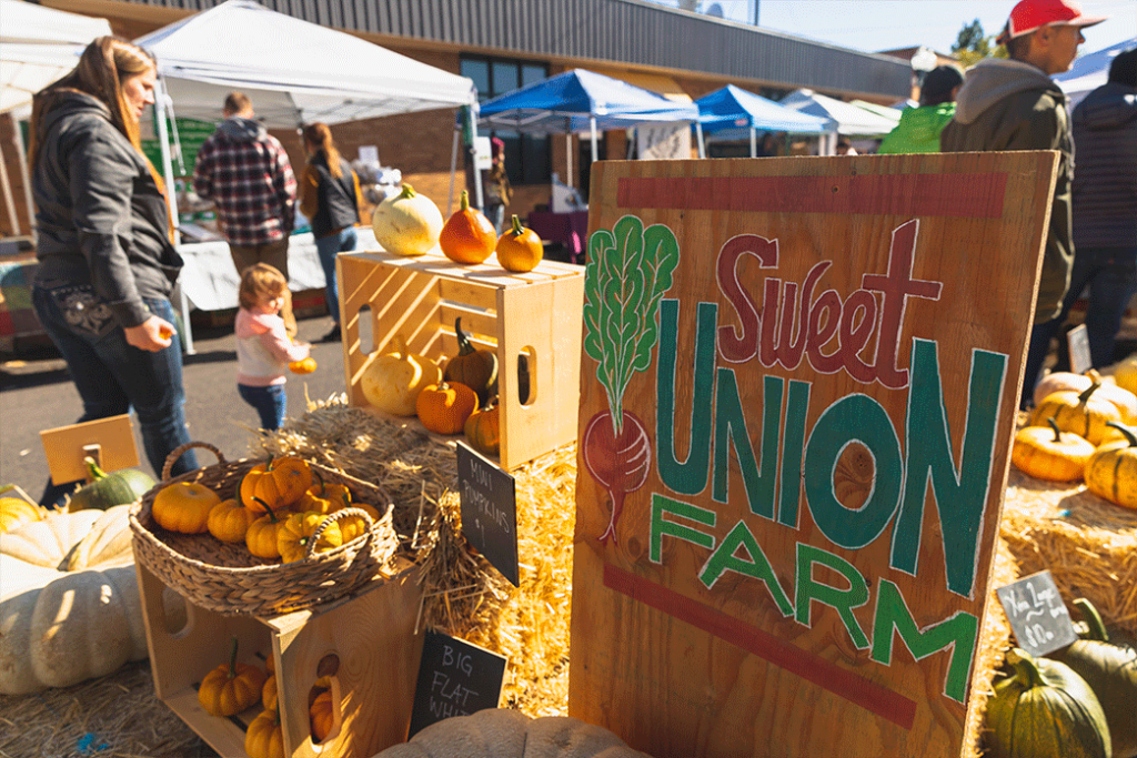 Saturday Farmer's Market in Klamath Falls, Oregon, showing a booth with bright orange, yellow, and green pumpkins, hay bales, and a sign for Sweet Union Farm.