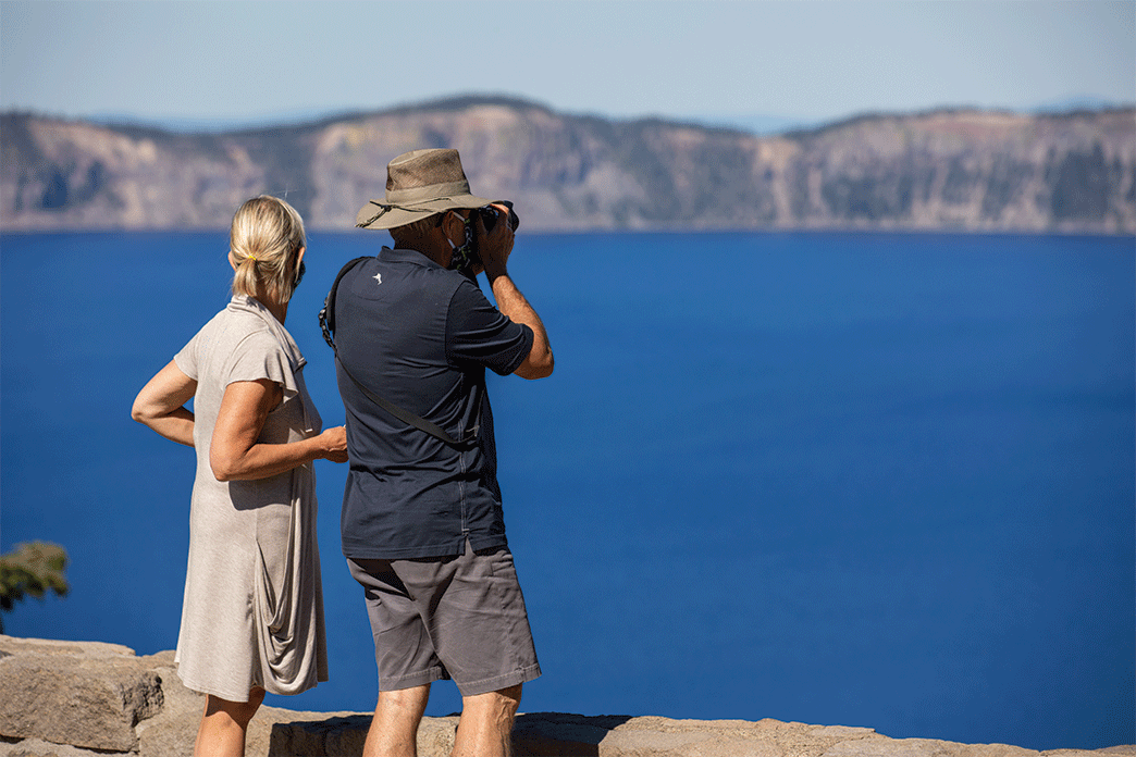 Couple take pictures of Crater Lake National Park with stunning blue water.