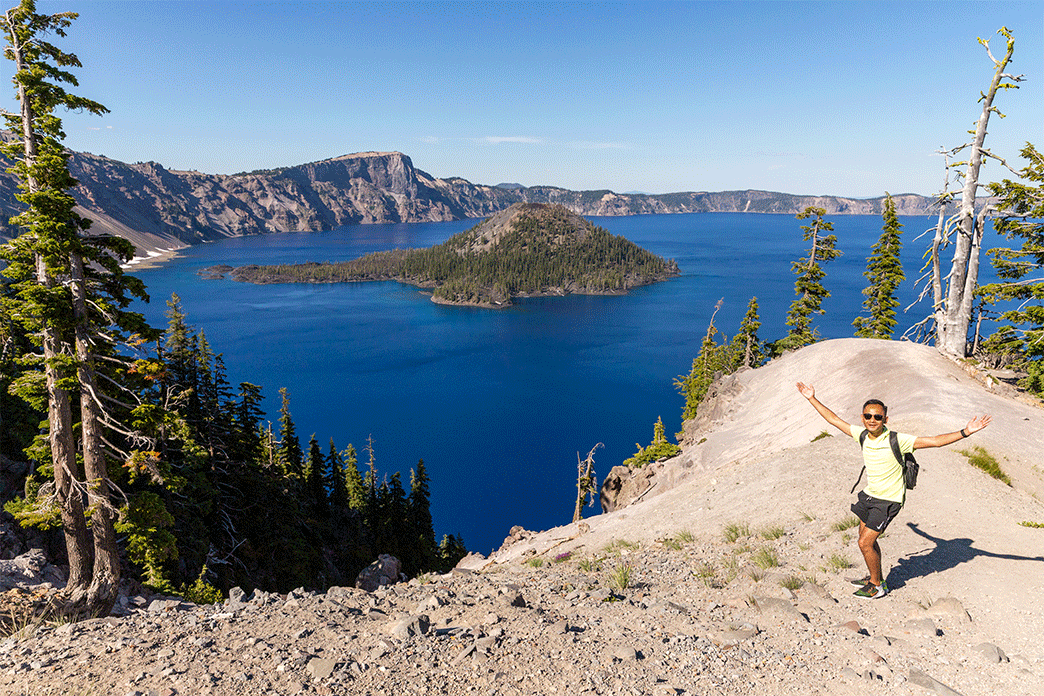 Asian man standing near edge of caldera of Crater Lake National Park with his arms in the air showing is crater lake worth seeing with Wizard Island in the background amid the crystal clear blue water of Crater Lake.