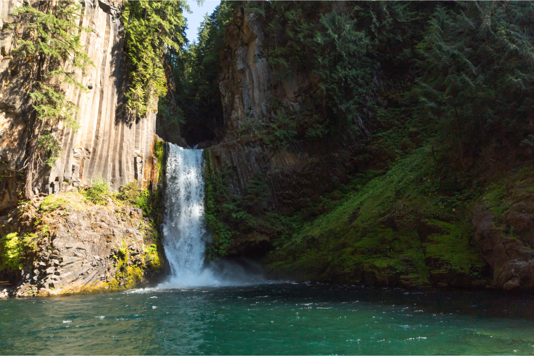 Toketee Falls, on the Umpqua Rivers, falls majestically into a crystal clear turquoise pool of water from a sheer wall of volcanic basalt.