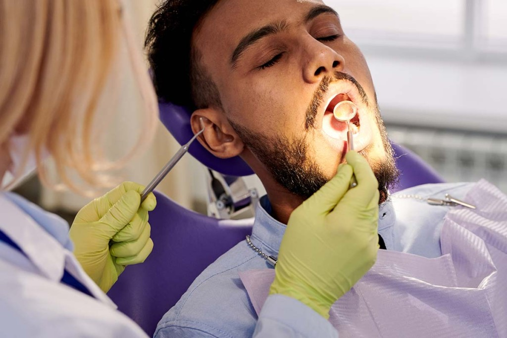 Dentist Performing Examination Inside Mobile Dental Outreach Facility