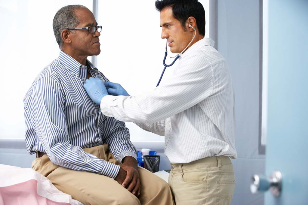 Doctor Listening To Patients Chest Inside Mobile General Medicine Wellness Clinic