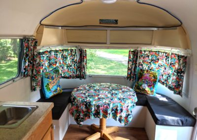 Airstream located at New River Gorge Campground looking to front at kitchen table and seating