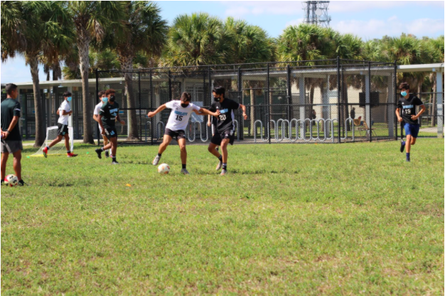 PASS TO ME: Senior center midfielder Carey McLeod focuses on breaking up the attack during after-school practice. McLeod has been playing since he was four and has shown an unwavering positive attitude on and off the field. (Photo courtesy of Tiffany Alfonso.)