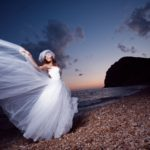 Bride posing showing her wedding dress on sunset beach