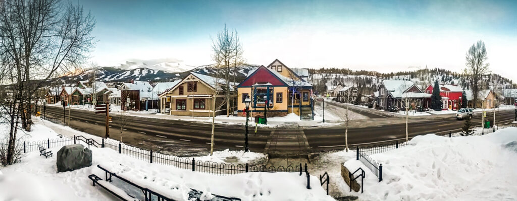 Panorama of buildings and snow on Main Street in Breckenridge, Colorado, with mountains in the background.