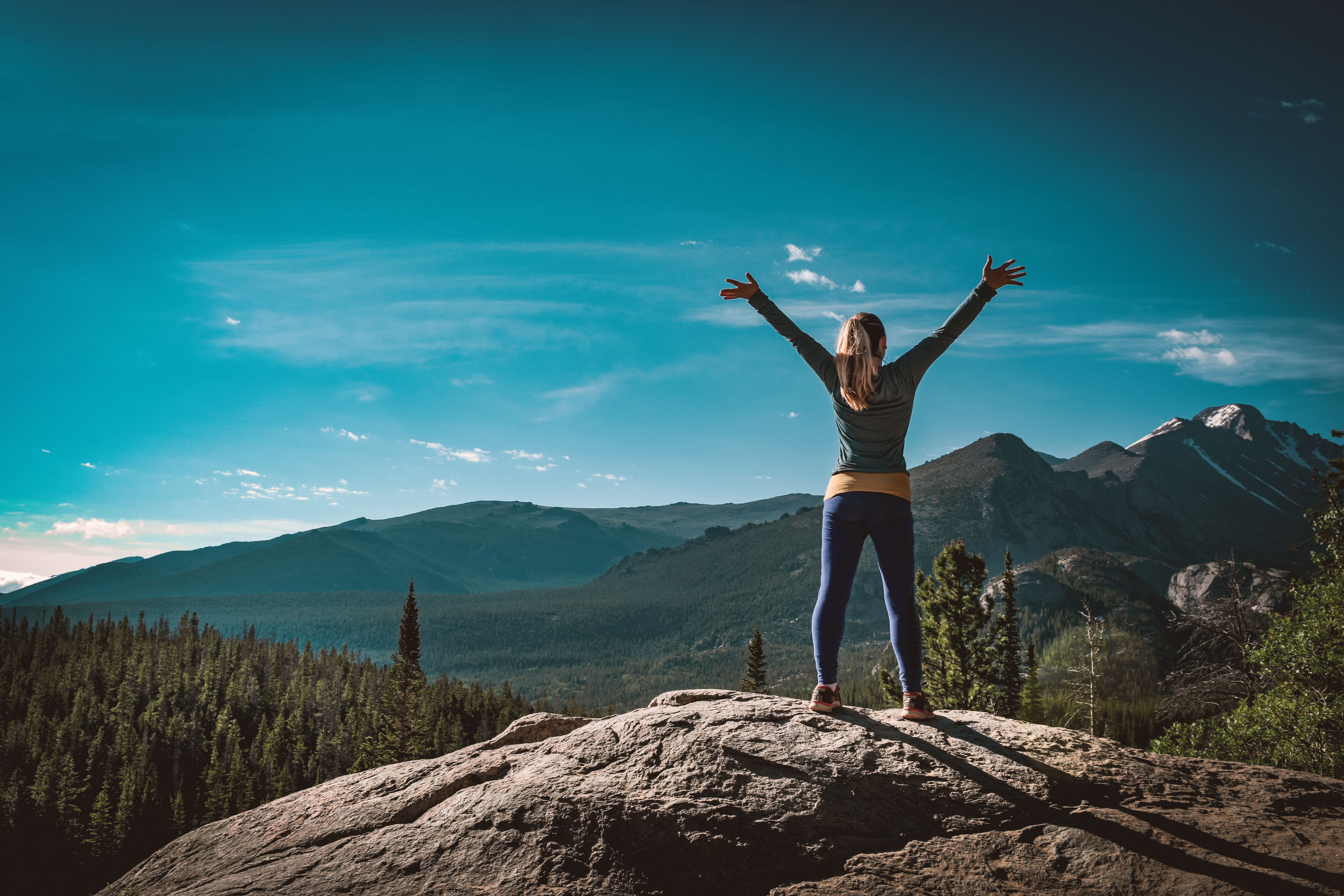 Kat stands atop a rocky bluff overlooking mountains