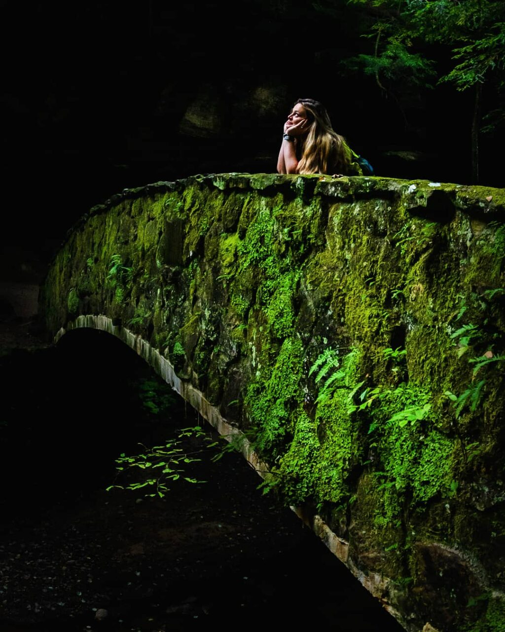 Woman looking longingly with her head in her hands on a stone bridge.