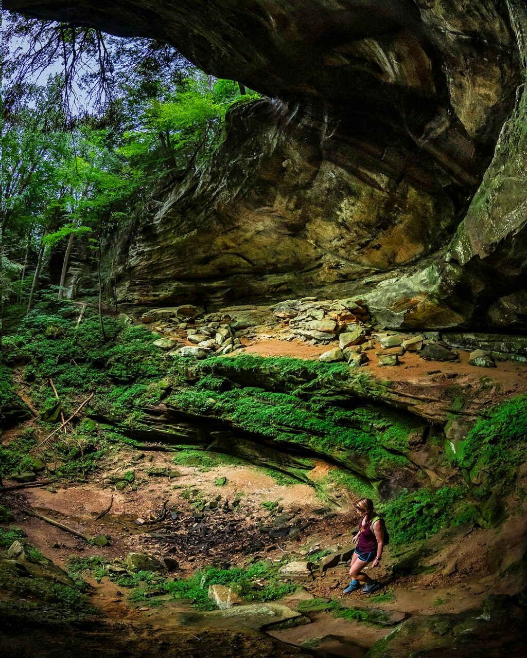 A woman hiker descends the ridged  bottom of a recess cave at Cantwell Cliffs.