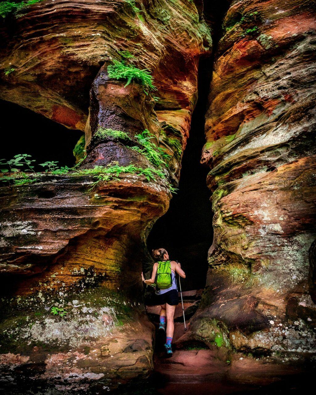 Woman hiker enters Rock House Cave.
